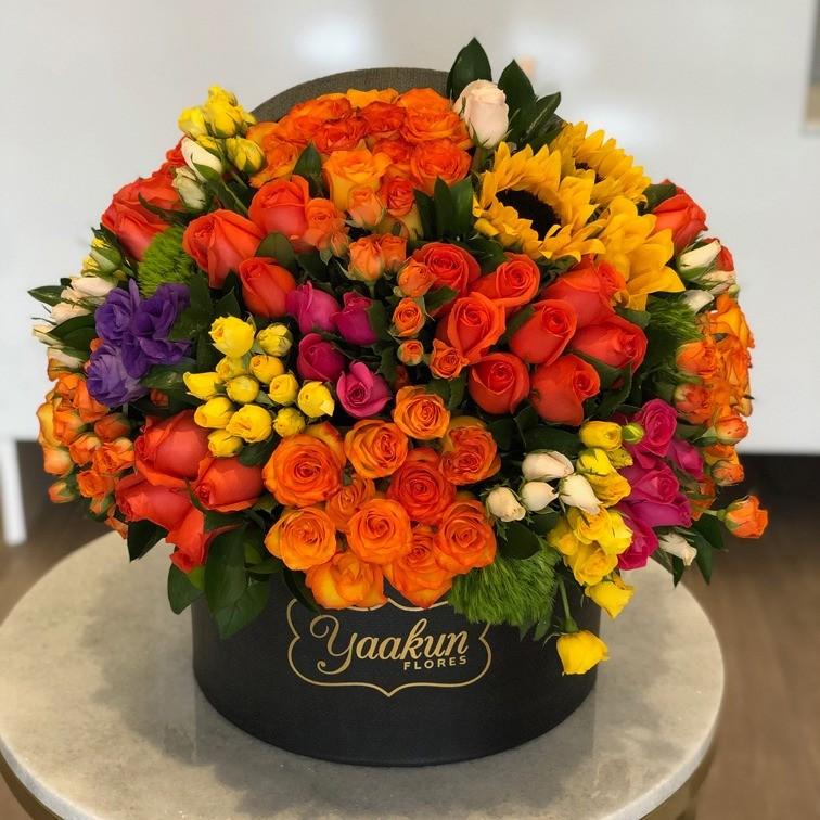 125 rosas y 10 girasoles en caja redonda media esfera primaveral