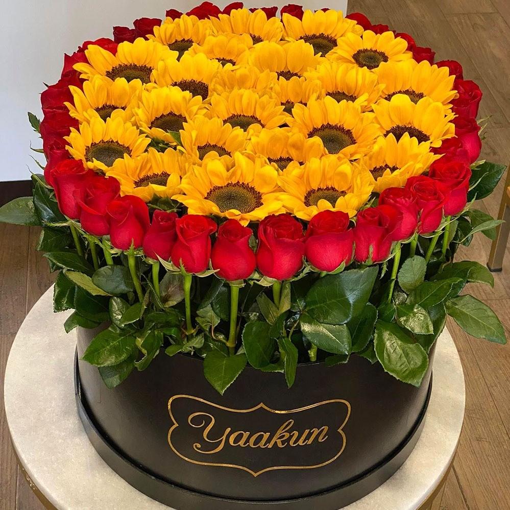 Caja redonda negra con girasoles y rosas amanecer soleado