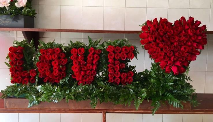 Arreglo de rosas en escultura love