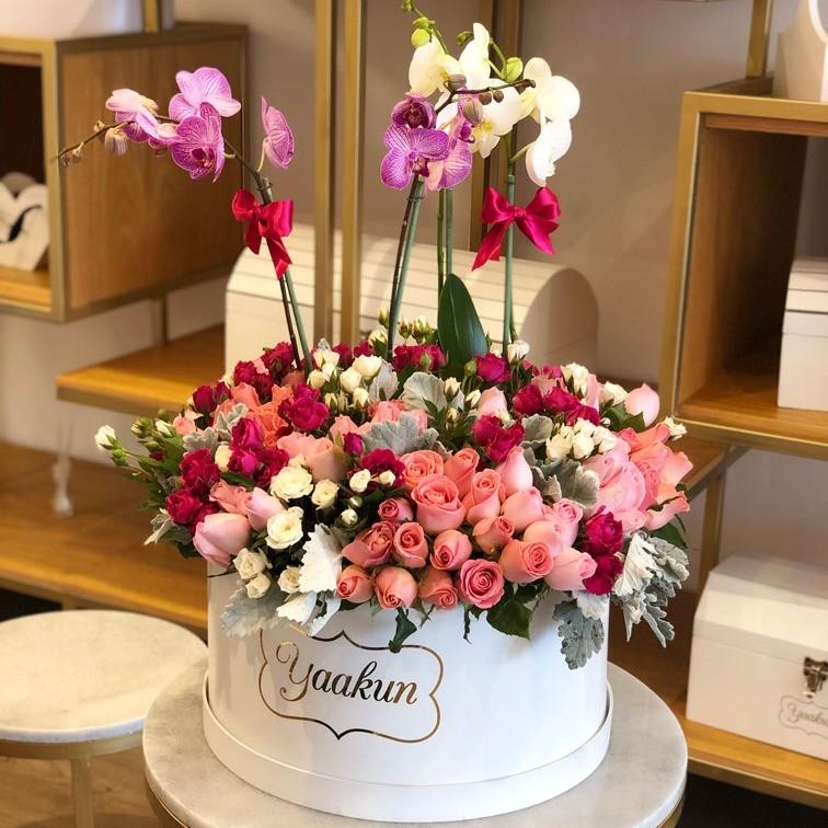 Orquídeas en caja grande con rosas y follajes finos